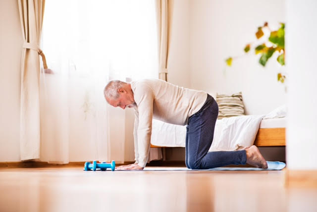 Active senior man doing exercise at home.
